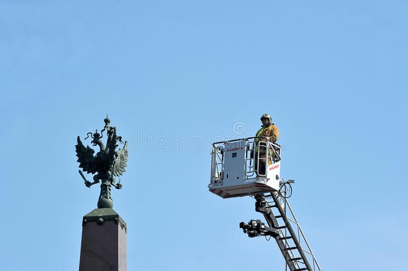 Fireman in a fire cradle looking at the coat of arms of the Russian Empire royalty free stock image