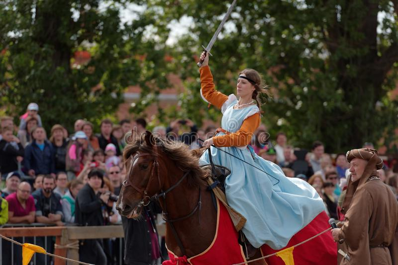 Lady competes in the contest on sword skills. St. Petersburg, Russia - July 9, 2017: Women in medieval clothes with sword on a horse during the festival Battle stock images