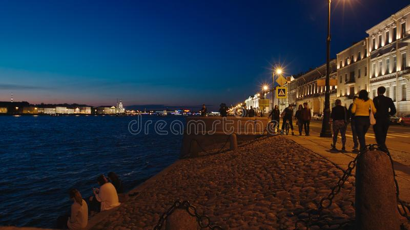 Illuminated stone embankment and tourists in the White Nights. ST. PETERSBURG, RUSSIA - JUNE 18, 2017: Illuminated stone embankment and tourists in the White stock image