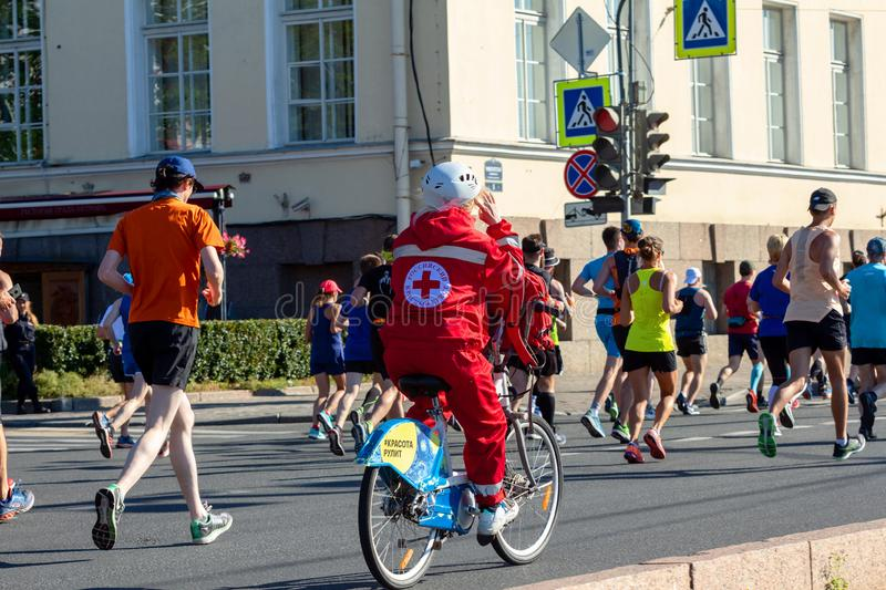 Woman medic in a helmet and red suit with a red cross emblem on the back riding a bicycle next to the runners stock image