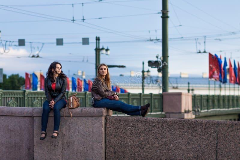 ST PETERSBURG, RUSSIA - 22 LUGLIO 2015: Due giovani donne graziose che si siedono sul recinto del granito del ponte fotografia stock