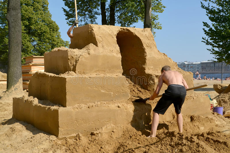 ST. PETERSBURG, RUSSIA. The man begins work on a sandy sculpture. ST. PETERSBURG, RUSSIA - JULY 13, 2014: The man begins work on a sandy sculpture. Annual stock image
