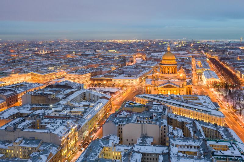 ST. PETERSBURG, RUSSIA - MARCH, 2019: Isaac Cathedral among roofs of buildings, St Petersburg, Russia at night royalty free stock photos