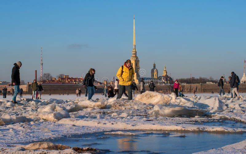 St Petersburg, Russia - 5 marzo 2017: Peter e Paul Fortress nell'inverno La gente sta camminando lungo il ghiaccio del Neva fotografia stock libera da diritti