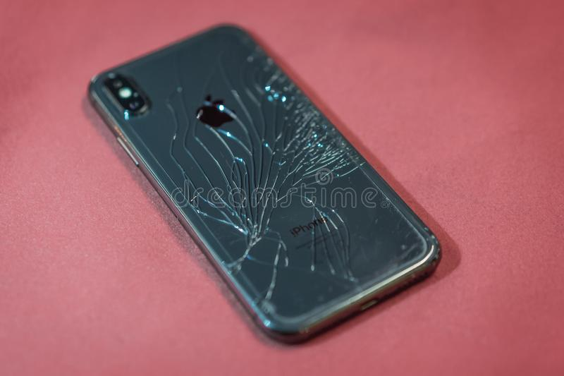 ST. PETERSBURG, RUSSIA - MAY 27, 2018: Black smartphone Iphone X broken glass on the back cover of the phone close up royalty free stock photography