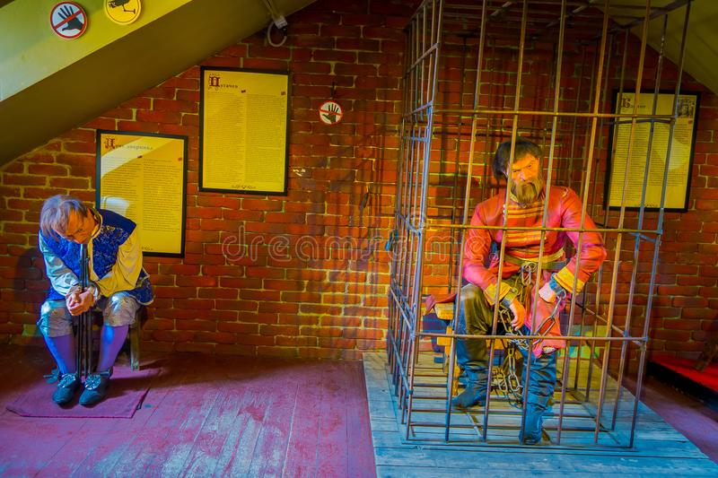 ST. PETERSBURG, RUSSIA, 17 MAY 2018: View of two wax sculpture one inside of jail and other with shackles in his hands. And feet inside of wax museum gallery royalty free stock images