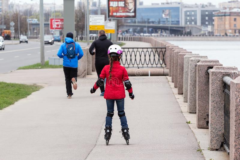 Girl in a red jacket and blue jeans rollerblading stock photography