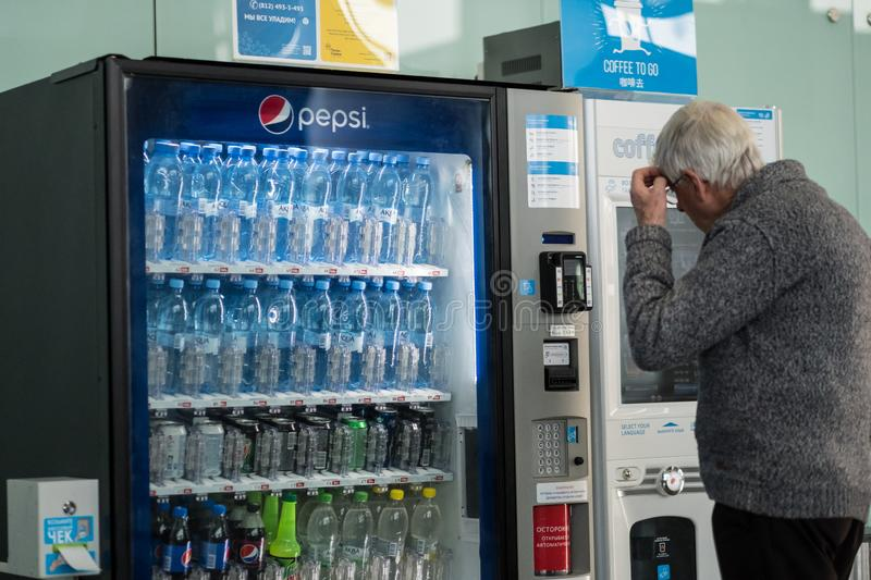 elderly man at the airport chooses a soft drink in a vending machine. Commercial stock photography