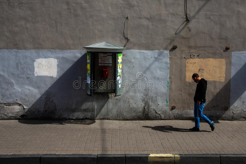 ST PETERSBURG, RUSSIE - JUIN, 13 2014 : Homme adulte avec des écouteurs marchant sur sideway près du mur peint avec l'appel-boîte photographie stock