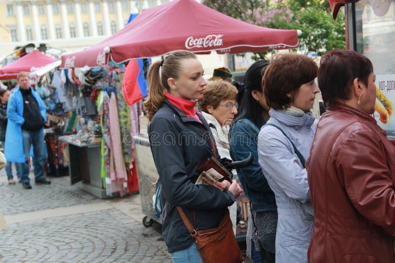 St Petersburg, Russie 12 juin 2015 : Les filles se tiennent sur le point d'avoir les hot-dogs près de la place de palais images libres de droits