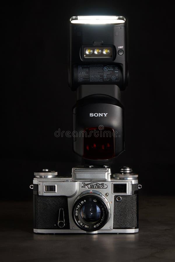 St Petersburg/Russische Föderation - 8. Februar 2019: alte Kamera Kiew mit modernem speedlight Sony auf dunklem Hintergrund lizenzfreie stockfotografie