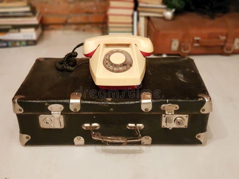 ST PETERSBURG, RUSSLAND: Alter sowjetischer Koffer und ein beige Drehtelefon an am 30. Januar 2019 lizenzfreies stockfoto