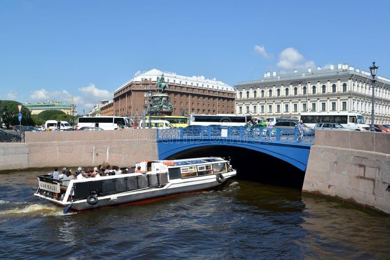 St. Petersburg, Russland Das Exkursionsschiff schwimmt unter blaue Brücke durch den Moika-Fluss am Sommertag lizenzfreies stockfoto