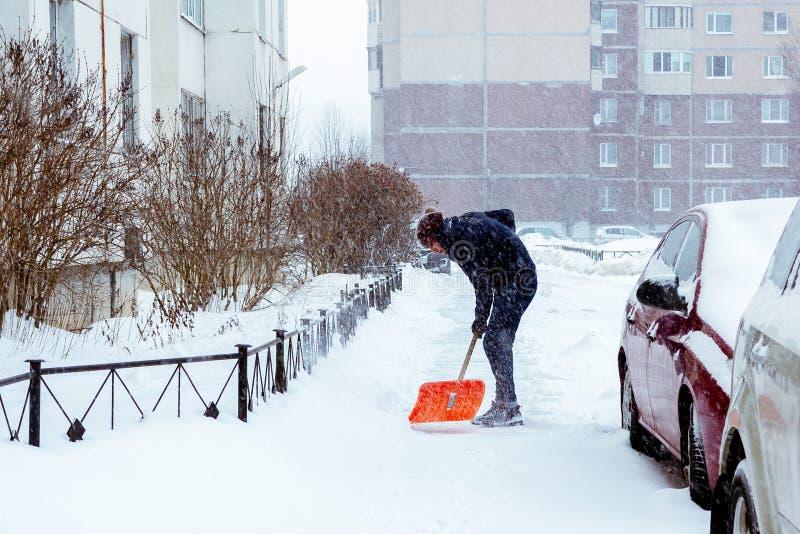 St Petersburg, Russland - 17. Januar 2019: Ein Mann säubert Schnee im Yard mit einer Schaufel nach schwere Schneefälle lizenzfreies stockfoto