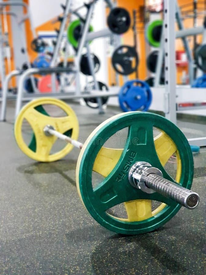 ST PETERSBURG, RUSSLAND: Sportausrüstung Barbell mit den gelben und grünen Disketten im sportclub St Petersburg, Russland an am lizenzfreie stockfotos