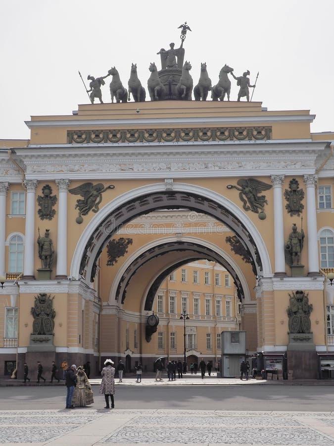 St Petersburg RYSSLAND – April 30, 2019: Bågen av huvudsakliga högkvarter som bygger med gataskådespelare i dräkter arkivfoton