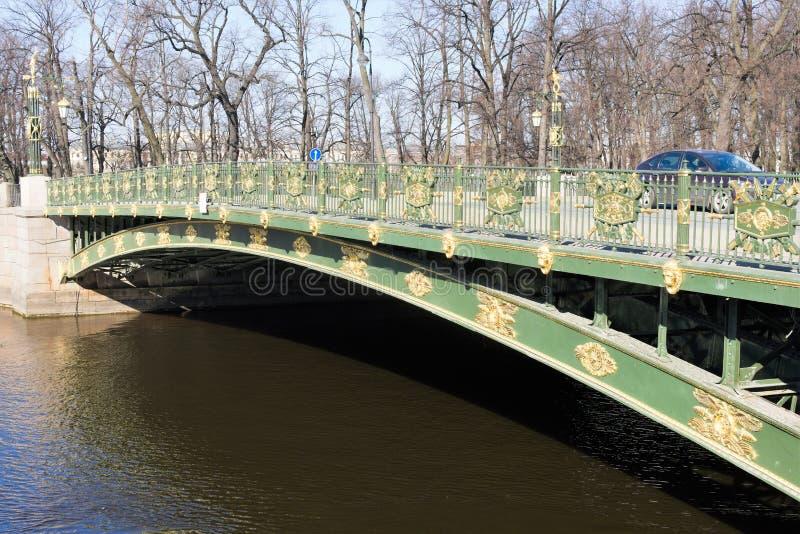 St Petersburg Ryssland, April 2019 Metallbro över en kanal i mitten av staden royaltyfri bild