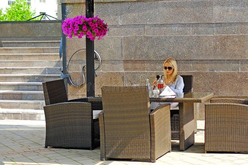 St Petersburg Ryssland 05 18 2018 en flicka i ett sommarkafé läsande SMS royaltyfri fotografi