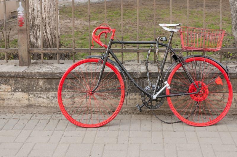St Petersburg Ryssland - 04 26 2019: F?rgrik gammal cykel n?ra staketet p? trottoaren i staden arkivbilder