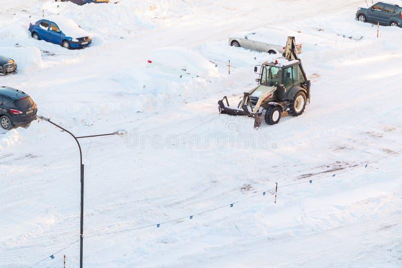 St Petersburg Ryssland - Januari 31, 2019: Traktoren tar bort insnöat parkeringsplatsen efter ett snöfall royaltyfri bild