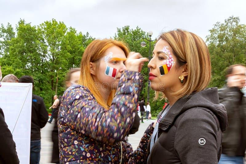St Petersburg Ryssland - Juli 10, 2018: flickahejaklacksledare på gatan som målas på kindflaggan av Belgien för en fotboll royaltyfri fotografi