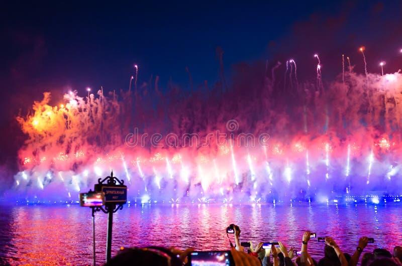 ST PETERSBURG RYSSLAND - JUNI, 2018: Folket som gör foto av fyrverkerier över den Neva floden på före detta elevberömscharlakansr royaltyfri bild