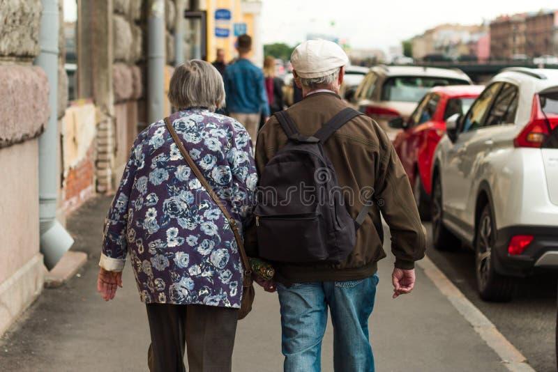 St Petersburg Ryssland, 27 Juni 2019 - par av äldre folk som går ner gatan som rymmer händer arkivbild