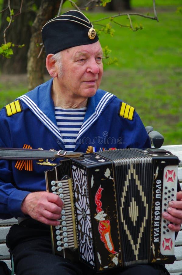 ST PETERSBURG RYSSLAND - MAJ 9, 2014: den angenäma veteran spelar dragspelet på årsdagen för th 69 av segern i världskriget II arkivfoton