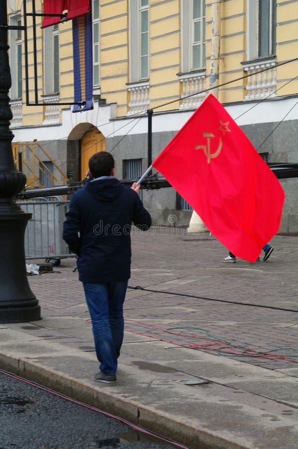 ST PETERSBURG RYSSLAND - MAJ 09, 2014: den ensamma mannen går med symboler för en sovjetisk röd flagga, hammare- och skärapå det  arkivbild