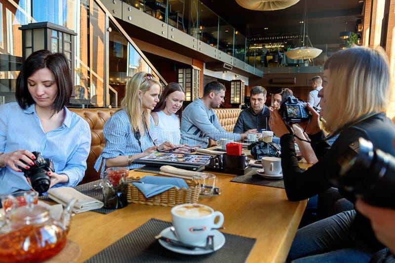 St Petersburg Ryssland-mars 24, 2019 En grupp av fyra affärspersoner som samlas på frukosttabellen som diskuterar intressera arkivfoton