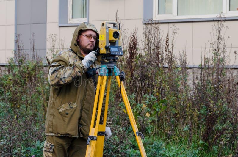 St Petersburg Ryssland-Oktober 23,2018 - inspektörarbetare med teodoliten arkivfoto