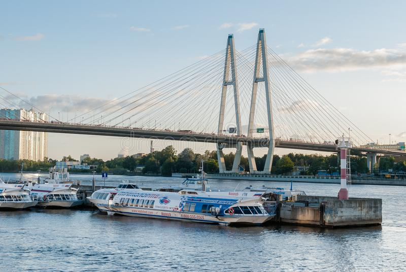 St Petersburg Ryssland - September 5, 2017: Stående bärplansbåtfartyg på flodhamnplatsen med en kabelbro i Sankt-Petersburg, R royaltyfri fotografi