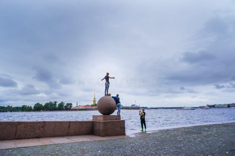 St Petersburg Sommar 2016 Ungdomarsom har gyckel som tar bilder på bollen som spottas av den Neva floden royaltyfria bilder