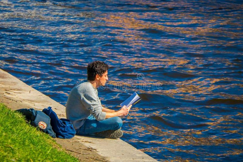 ST PETERSBURGO, RÚSSIA, O 2 DE MAIO DE 2018: Homem não identificado que senta-se na beira do rio de Moika que lê um livro e imagem de stock royalty free