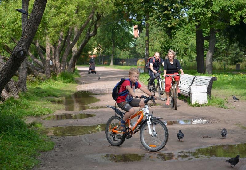 ST Petersburgo, Rusia La familia en bicicletas va en una trayectoria del parque Foco en la mujer foto de archivo