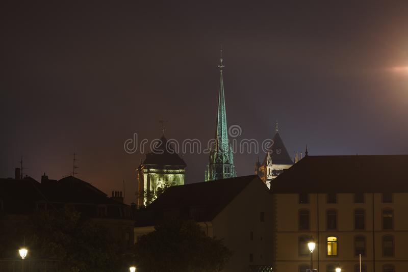 St. Pierre Cathedral St. Peter`s Cathedral spire highlighted above Geneva city at night, Geneva, Switzerland royalty free stock images