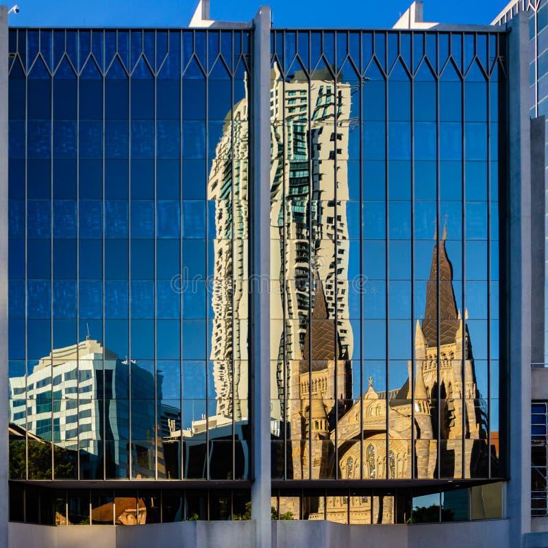 St Stepehens Kathedraal in een gebouw dat van Brisbane wordt weerspiegeld CDB stock afbeeldingen