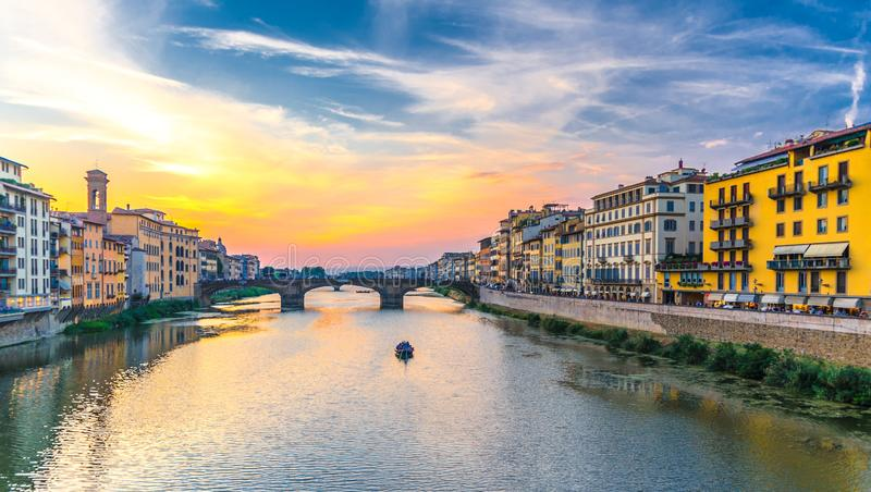 St Trinity Bridge stone bridge and boat on Arno River water and embankment promenade with buildings in historical centre of Floren stock photography