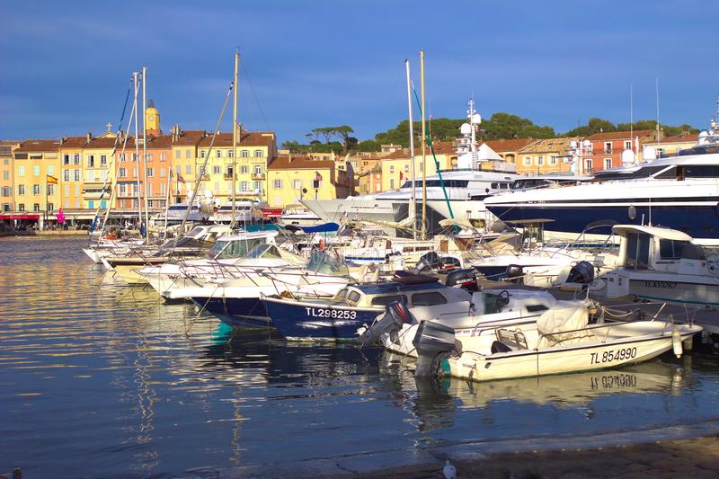 ST TROPEZ, FRANCE, JUNE 04 2016: Modern boats in the harbour in front of traditional Provence houses stock image