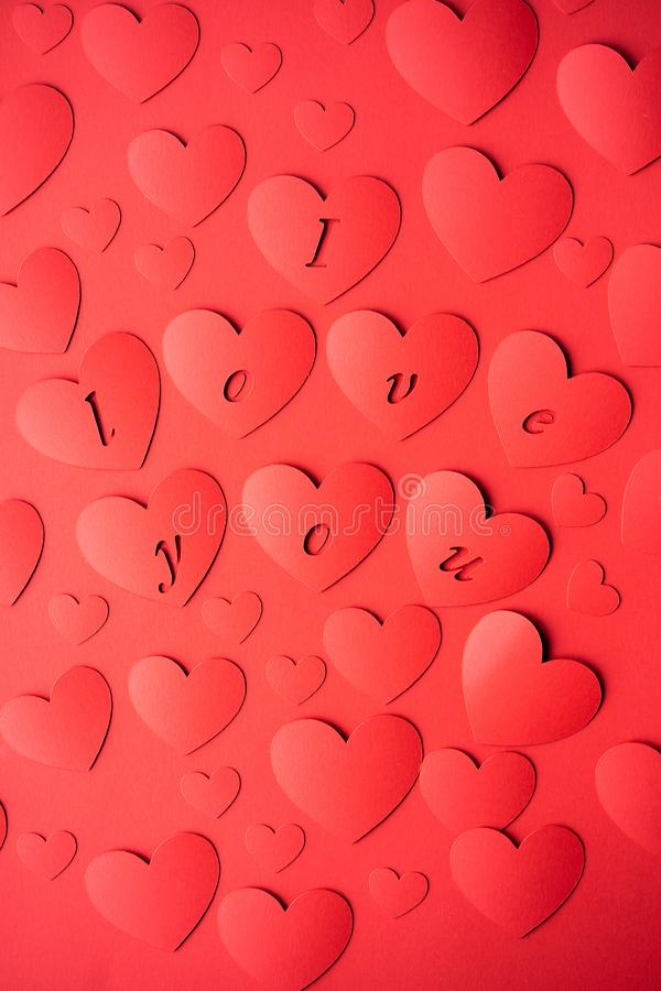 Valentine`s day concept. The background is red, the red hearts are cut out of paper. Words I love you. St. Valentine`s day concept. The background is red, the stock images