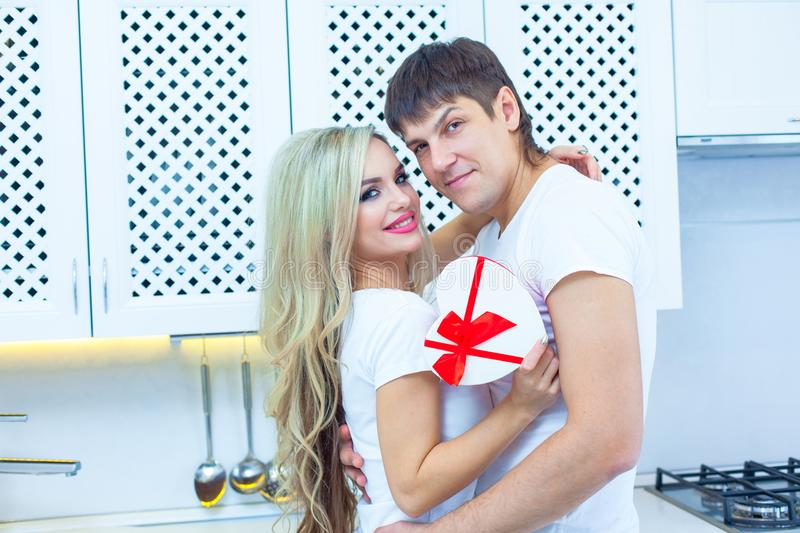 St. Valentine`s day love. 14 February. Handsome young man giving present to beautiful woman at home in the kitchen stock photos