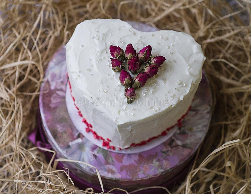 St. Valentine`s Day, Mother`s Day, Birthday Cake. A festive dessert in the shape of heart. White cake decorated by dry roses on. St. Valentine`s Day, Mother`s royalty free stock photography