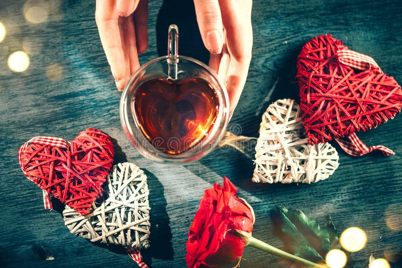 St. Valentine`s Day scene. Woman`s hands holding heart shaped tea cup with rattan red hearts decor over dark wooden background royalty free stock photo