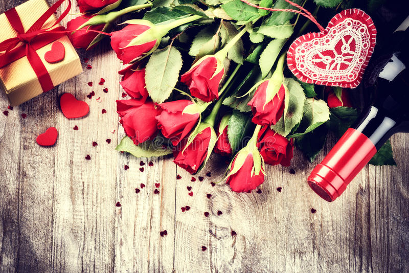St Valentine's setting with red roses bouquet, present and red w. Ine bottle. Copy space stock images