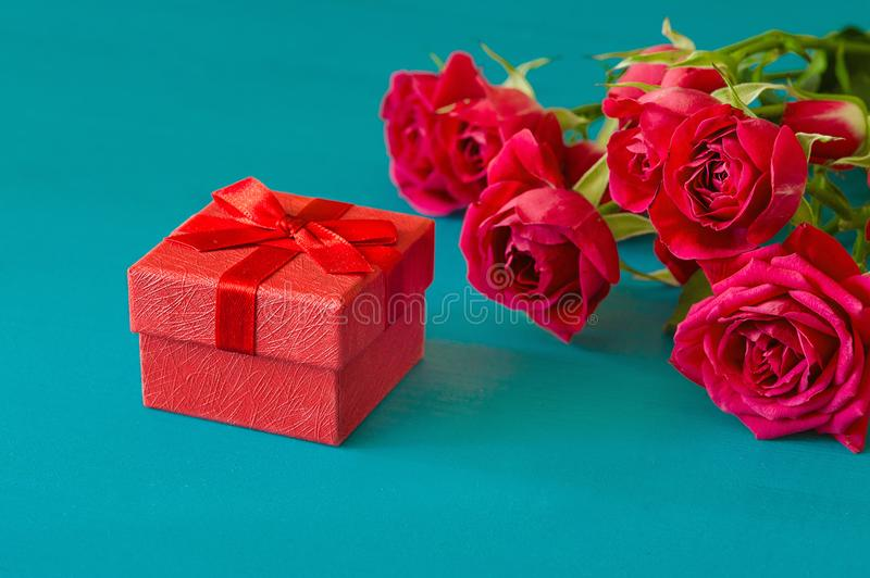 St. Valentines Day concept. Fresh red roses and gift box on wooden table royalty free stock photos