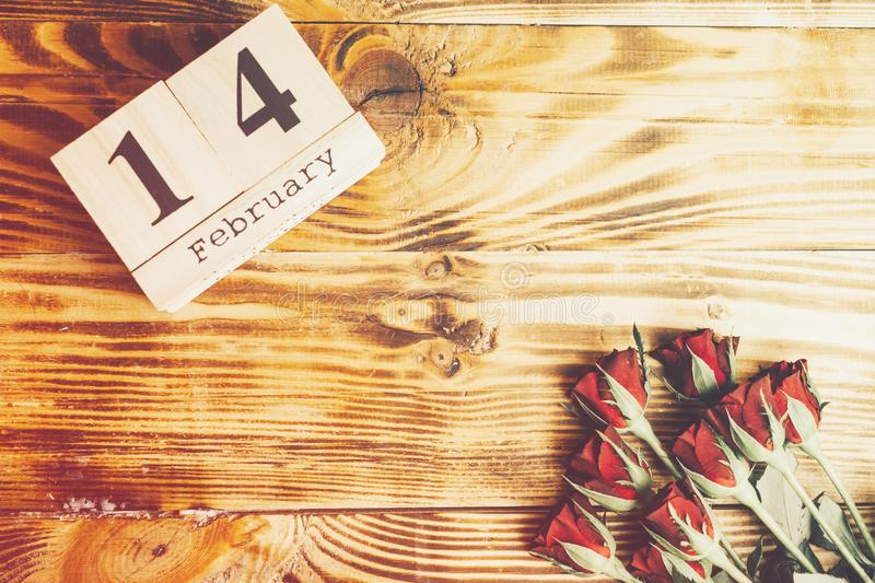 St. Valentines day minimal concept on wooden background. Red roses and wooden caledar with 14 february on it stock images