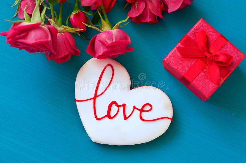 St.-Valentinsgruß-Tageskonzept Frische rote Rosen und Geschenkbox und Lebkuchen mit der Aufschrift lieben auf Holztisch oberseite stockbild