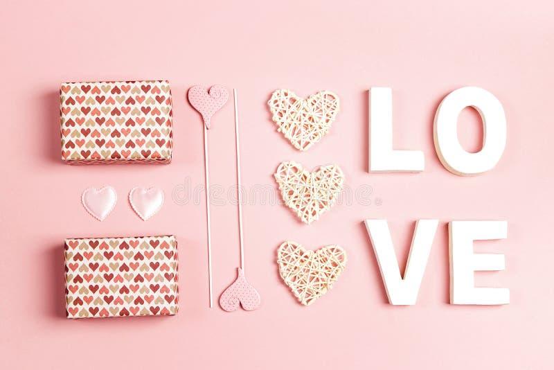 St walentynek dnia skład z słowo miłością, prezentami i dekoracyjnymi sercami na różowym tle, zdjęcia stock