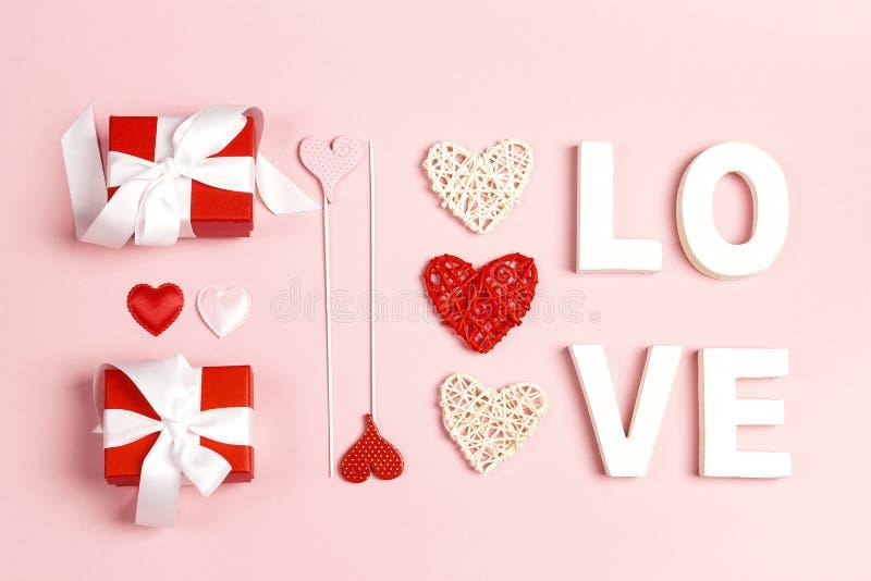 St walentynek dnia skład z słowo miłością, prezentami i dekoracyjnymi sercami na różowym tle, obrazy stock