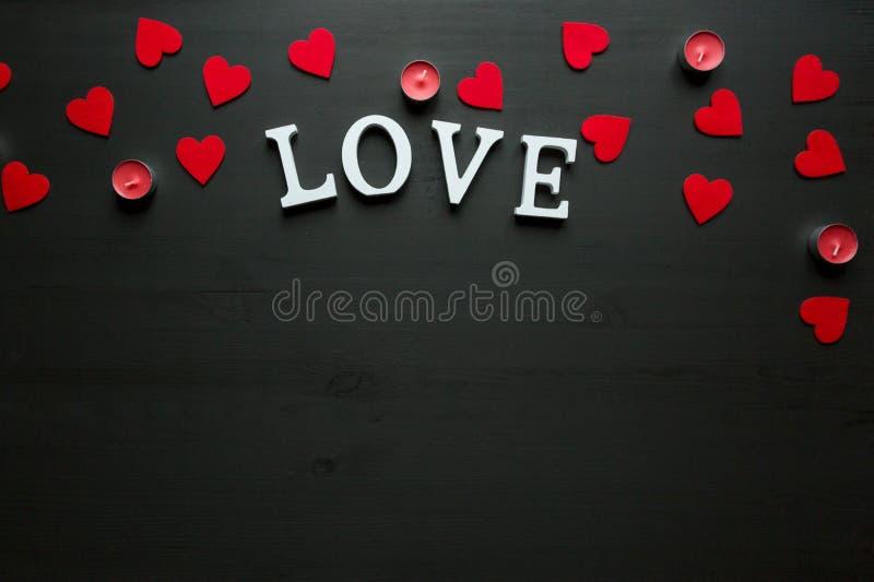 St walentynki ` s dnia pojęcie słowo miłość kłaść na drewnianym plecy mlejącym z czerwonymi świeczkami i sercami fotografia stock